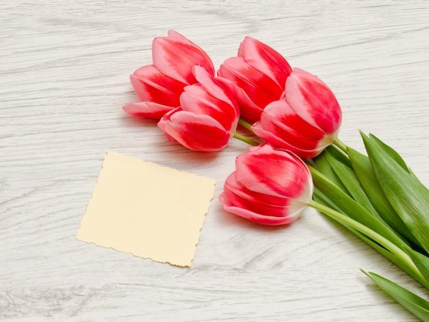 Pulisca la carta, tulipani rosa su un fondo di legno leggero. vista dall'alto, spazio per il testo