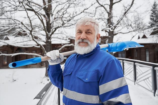 Pulitore in tuta da lavoro con pala per rimuovere la neve.