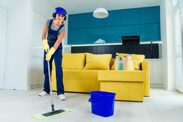 Pulitore professionale femminile giovane bella in uniforme speciale con le cuffie che lava il pavimento con la zazzera ed ascolta musica all'appartamento.