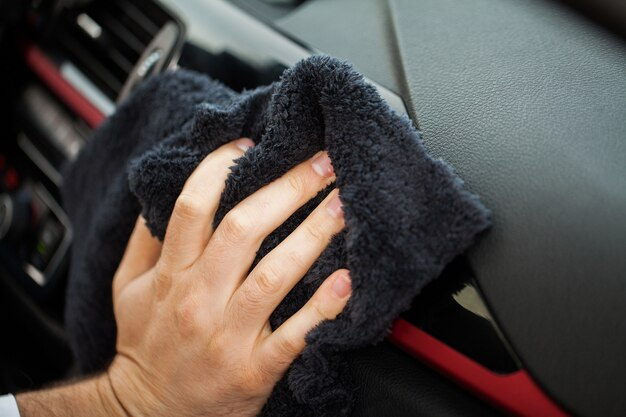 Pulizia auto. mano con panno in microfibra per pulizia interni auto
