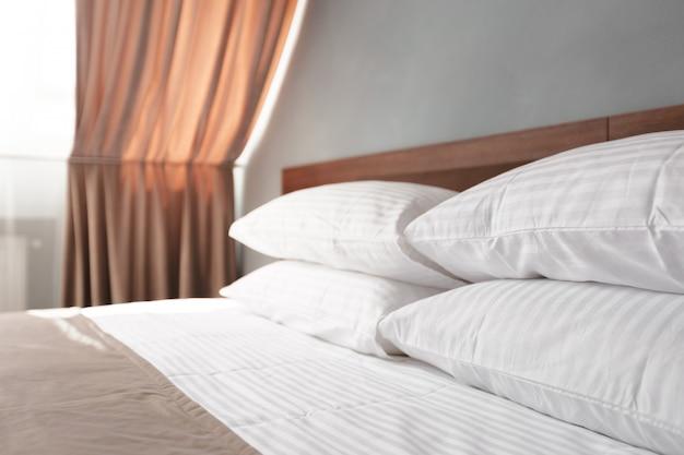 Pulizia del letto con cuscini bianchi puliti e lenzuola nella beauty room.