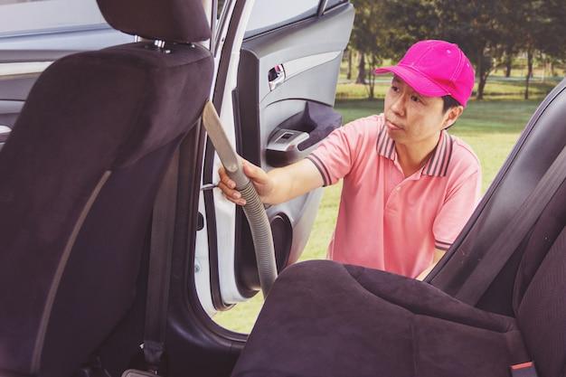 Pulizia del personale di servizio auto degli interni della vettura con aspirapolvere