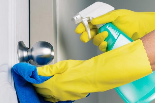 Pulizia del pomello della porta con alcool spray per la prevenzione del coronavirus covid-19