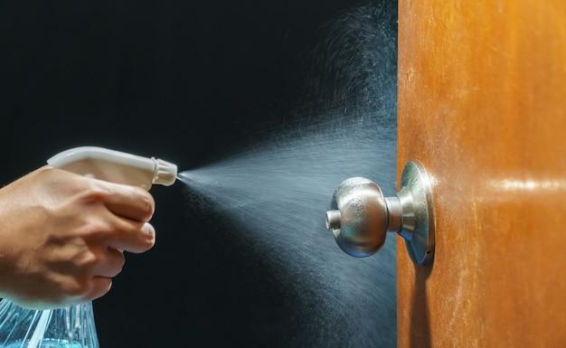 Pulizia del pomello della porta con alcool spray per la prevenzione di covid-19 (coronavirus)