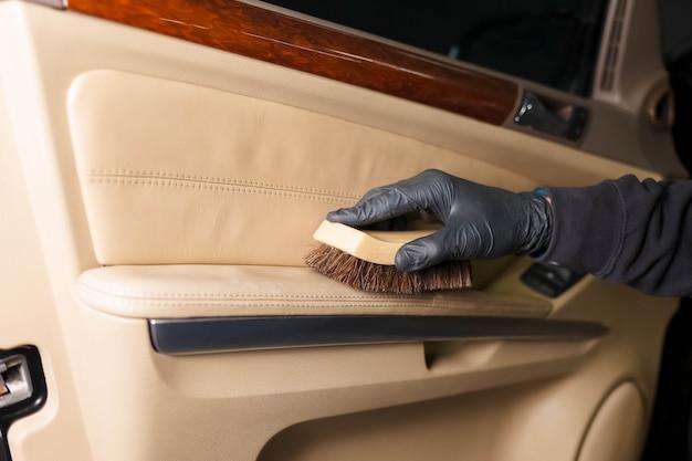 Pulizia del rivestimento della portiera dell'auto con una spazzola. concetto di detaling