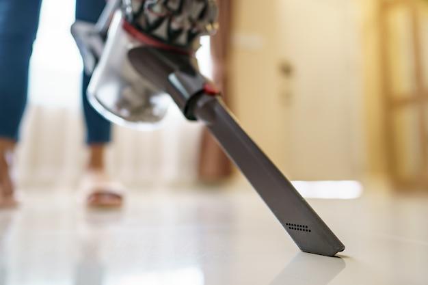 Pulizia dell'aspirapolvere di uso della donna sul pavimento.