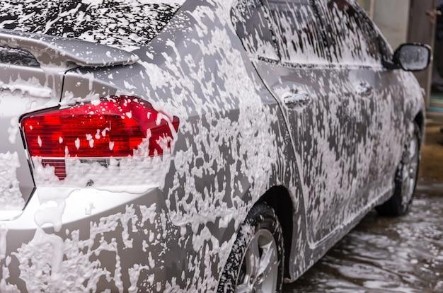 Pulizia dell'auto con schiuma, negozio di lavaggio auto