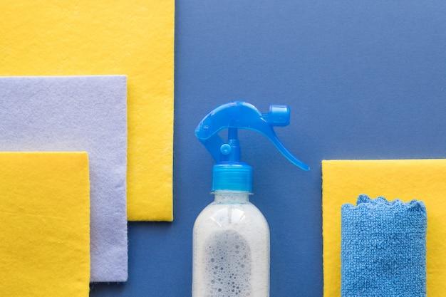 Pulizia della casa e pulizie, sfondo blu. detersivi per la pulizia o la disinfezione della stanza. bottiglie, rag, disinfezione domestica. detergente spray, spugna per pulizia con spazio copia, vista dall'alto.