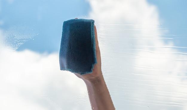 Pulizia della casa, lavaggio del vetro, mano femminile con uno straccio all'esterno della finestra
