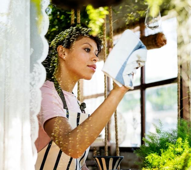 Pulizia della donna di origine africana che pulisce vetro del negozio