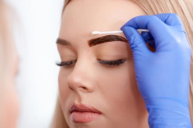 Pulizia della faccia del cliente durante il make-up permanente.