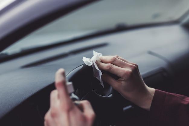 Pulizia della superficie dell'auto con spray alcolico