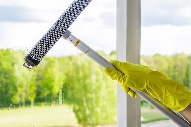 Pulizia delle finestre. una donna spruzza un detergente sul vetro.