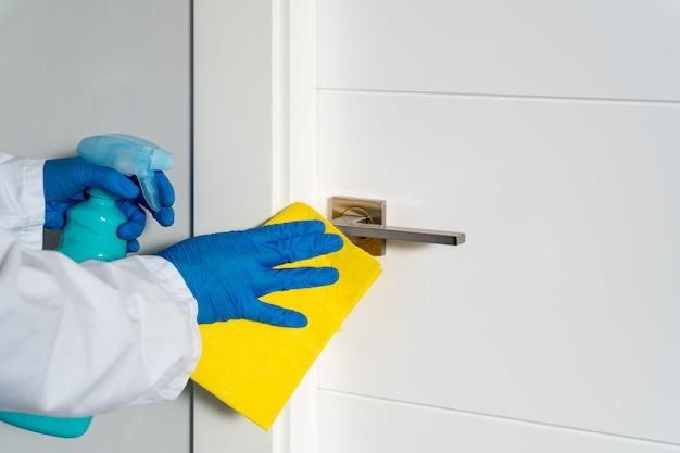 Pulizia delle maniglie delle porte con un antisettico durante un'epidemia virale
