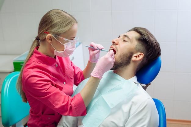 Pulizia professionale dei denti, il dentista pulisce i denti di un paziente maschio.