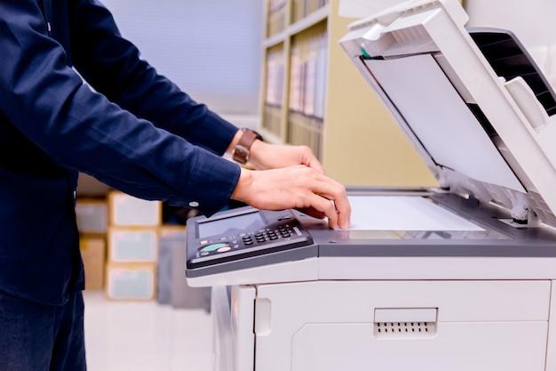 Pulsante di mano dell'uomo d'affari sul pannello della stampante