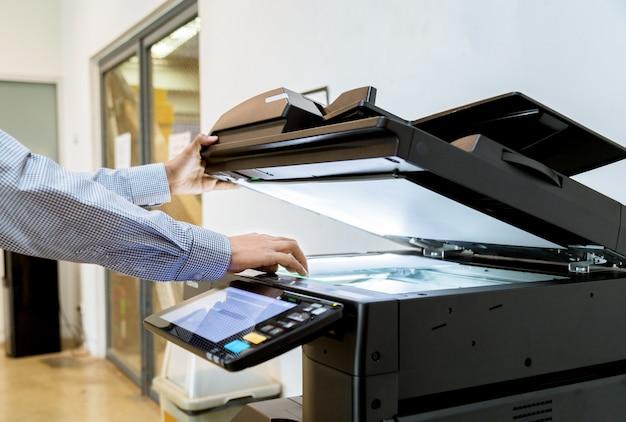 Pulsante di mano dell'uomo d'affari sul pannello della stampante.