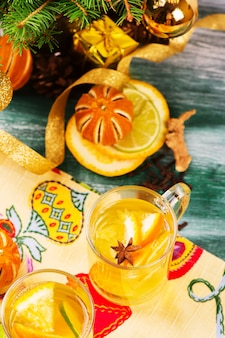 Punch arancione caldo con spezie in tazze di vetro sul tavolo di legno.