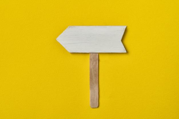 Puntatore a freccia in legno su giallo