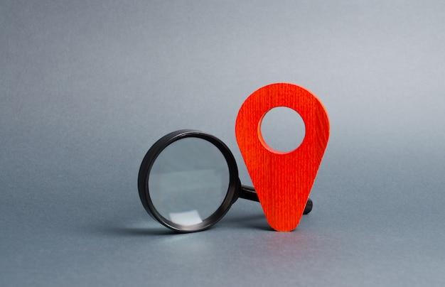 Puntatore rosso posizione e una lente d'ingrandimento su un grigio. turismo e viaggi