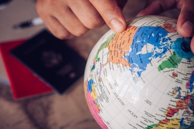 Puntatori ravvicinati sul globo, i turisti stanno pianificando di trovare attrazioni: conception travel