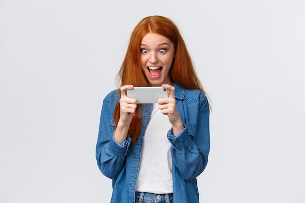 Punteggio battito studentessa eccitato, felice e sorpreso bella rossa, vinto competizione, sfida nel gioco smartphone, tenendo il telefono in orizzontale, guarda video divertenti da festa, guarda display stupito