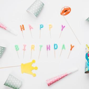 Puntello; corno di partito e cappello del partito intorno alle candele buon compleanno su sfondo bianco