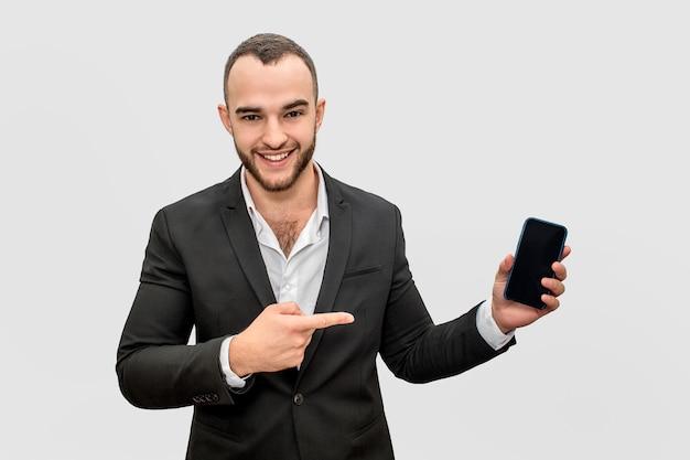 Punti felici dell'uomo d'affari sul telefono. lo tiene in mano. il giovane osserva sulla macchina fotografica e sorride.