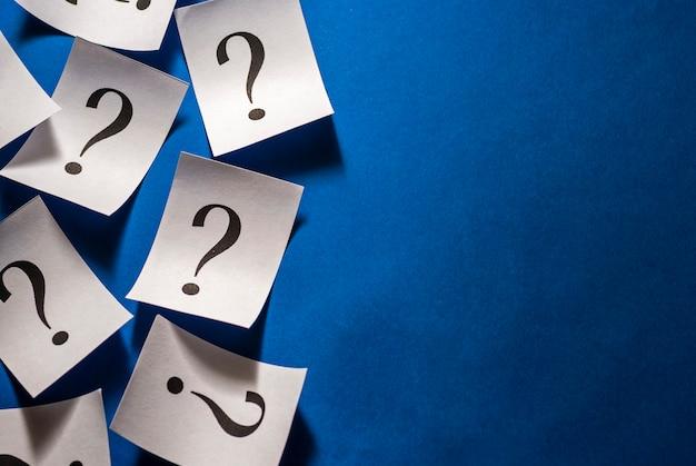 Punti interrogativi stampati su carte bianche su blu