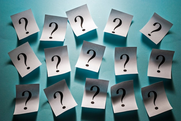 Punti interrogativi stampati su cartoncini bianchi