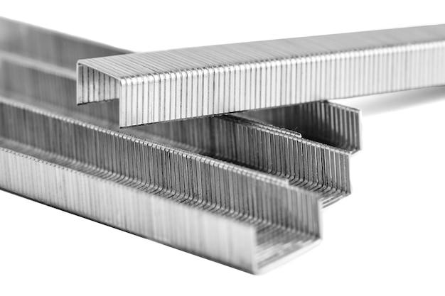 Punti metallici per cucitrice, primo piano isolato su bianco