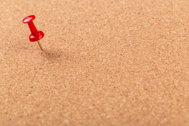 Puntina rossa appuntata su sfondo bacheca