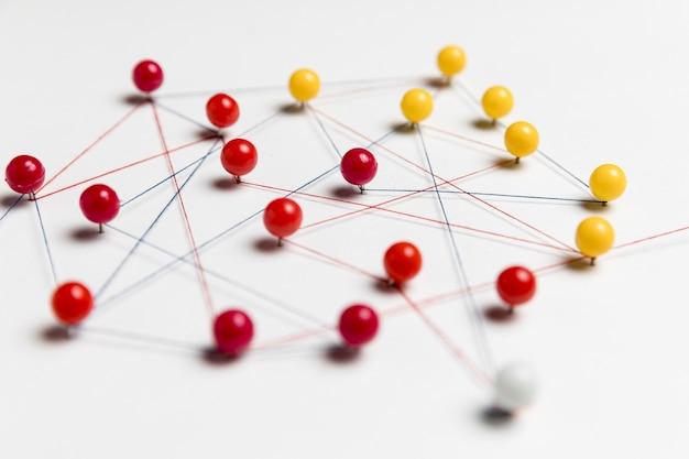 Puntine da disegno gialle e rosse con filo per la mappa del percorso