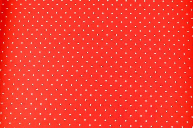 Puntini bianchi su sfondo rosso in tessuto a pois e trama