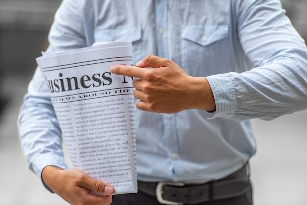 Punto dell'uomo d'affari al suo giornale per la lettura delle notizie negli affari.