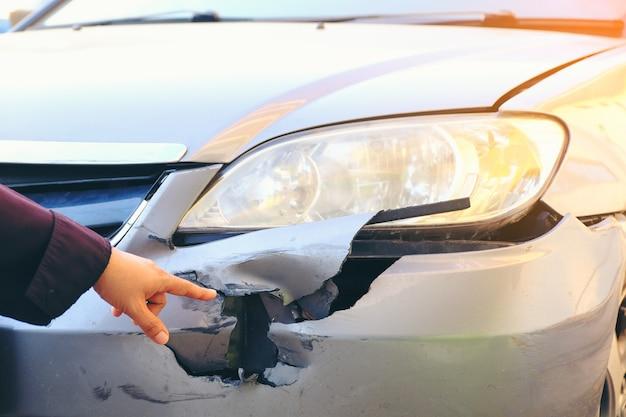 Punto della mano sul lato anteriore della macchina incidente. auto danneggiate da incidenti stradali