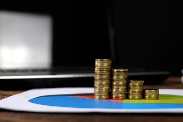 Punto delle pile delle monete con il computer portatile del taccuino e il grafico finanziario
