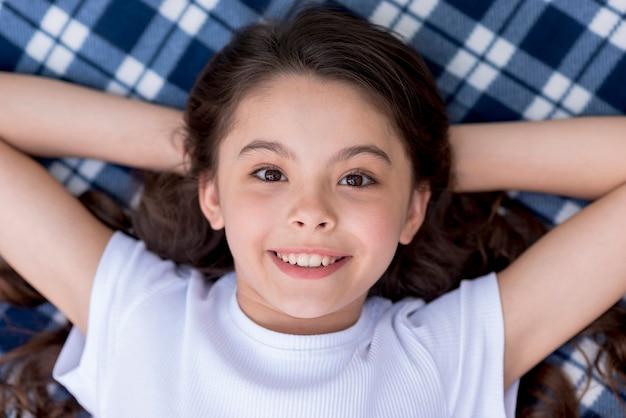 Punto di vista ambientale della ragazza graziosa sorridente che esamina macchina fotografica che si trova sulla coperta a quadretti