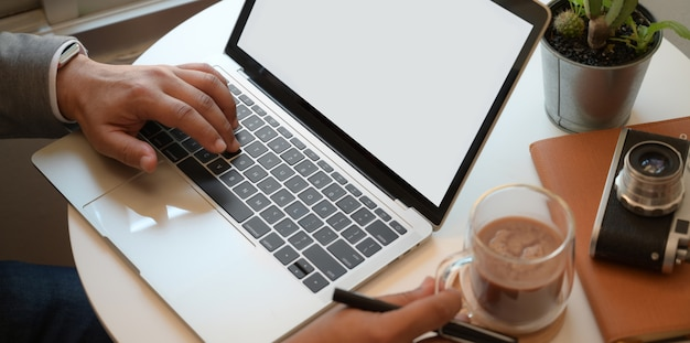 Punto di vista del primo piano dell'uomo d'affari che lavora con il computer portatile mentre tenendo una tazza di cacao caldo