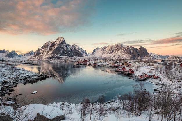 Punto di vista del villaggio di reine con la catena montuosa della neve sulla linea costiera alle isole di lofoten