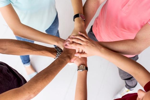 Punto di vista dell'angolo alto degli amici che impilano insieme le loro mani