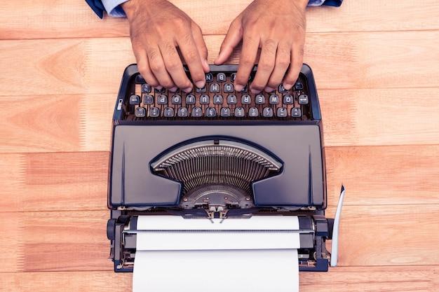 Punto di vista dell'angolo alto dell'uomo d'affari che scrive sulla macchina da scrivere allo scrittorio in ufficio