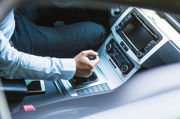 Punto di vista dell'angolo alto della mano di un uomo che cambia marcia in automobile