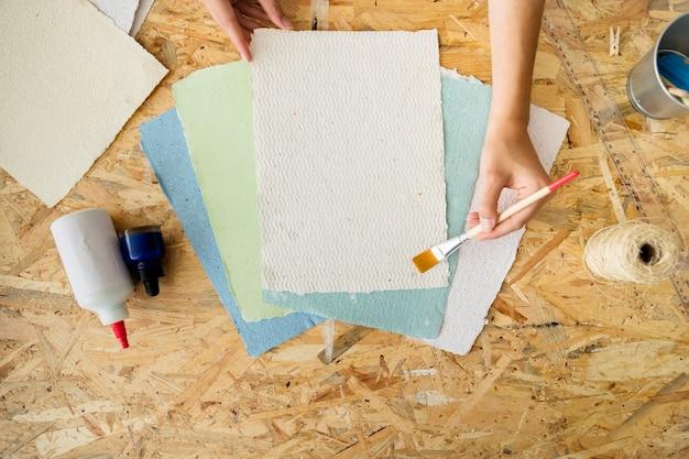 Punto di vista dell'angolo alto della mano di una femmina facendo uso del pennello sopra le carte fatte a mano