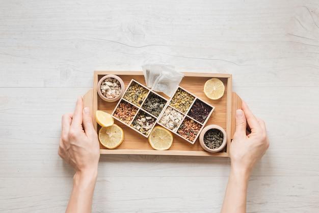 Punto di vista dell'angolo alto della mano di una persona che tiene vassoio di legno con le erbe e le foglie di tè asciutte