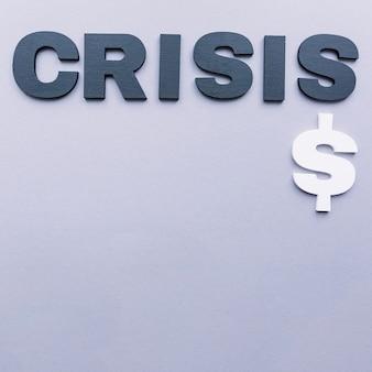 Punto di vista dell'angolo alto della parola di crisi con il simbolo di dollaro sul contesto grigio