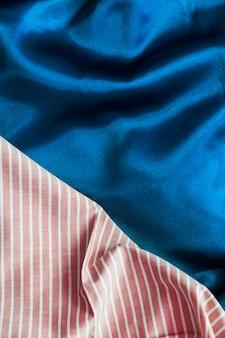 Punto di vista dell'angolo alto della tessile del modello delle bande sul panno blu regolare