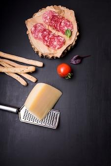 Punto di vista dell'angolo alto delle merguez sul sottobicchiere di legno con il pomodoro; grissini; formaggio e grattugia