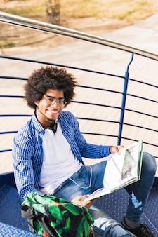 Punto di vista dell'angolo alto dello studente maschio dell'università con il libro e della borsa che si siedono sulla scala all'aria aperta