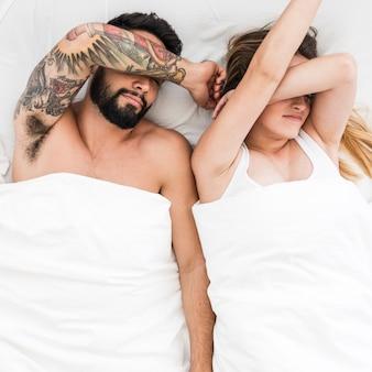 Punto di vista dell'angolo alto di giovani coppie che dormono sul letto